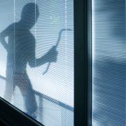 Einbrecher hinter Fenster.
